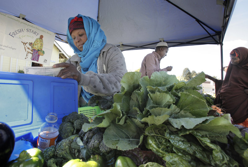 Seynab Ali, left, and Mohammed Abukar sell produce Wednesday at the community garden on Boyd Street in Portland. The two sell vegetables they grow as part of a farmer's collective called Fresh Start Farms at a farm in Lisbon.