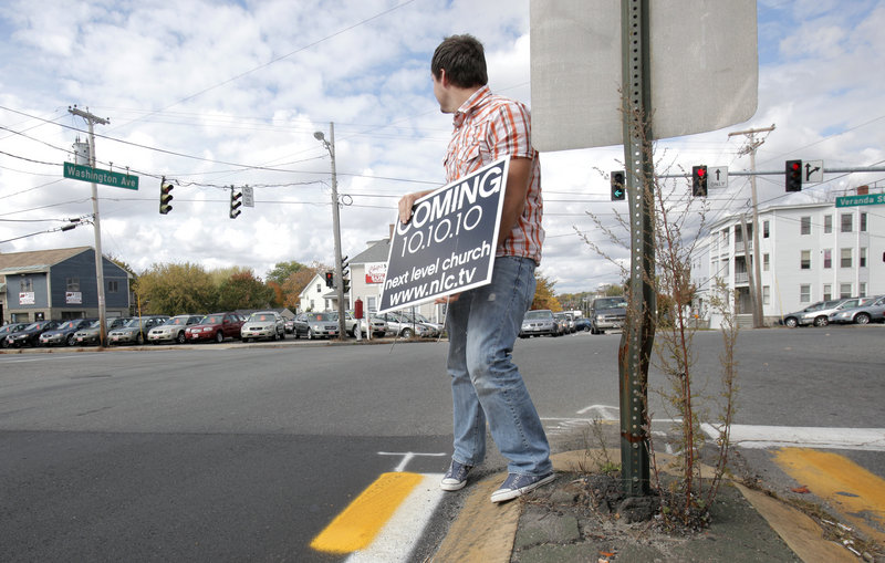 Allen Robbins, the local pastor of the Next Level Church, removes a sign announcing the opening of the church from the median of Washington Avenue in Portland on Thursday.