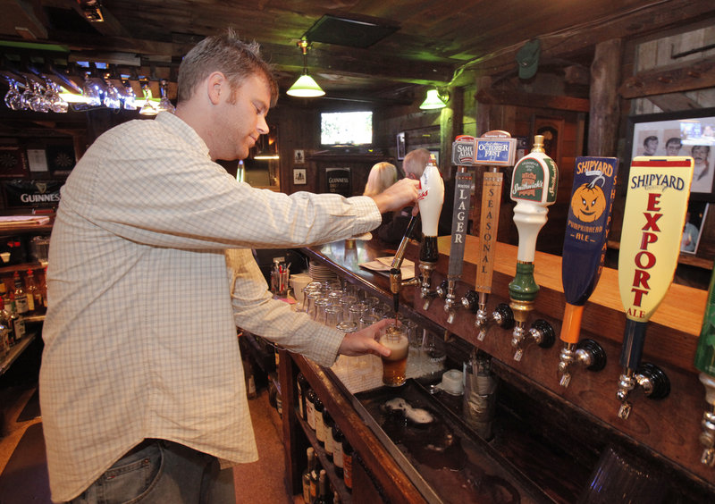 Ryan Kerry pours a black and tan at The Kerrymen Pub in Saco. The pub's autumn version of the longtime favorite is half Shipyard Pumpkinhead ale and half Guinness stout.