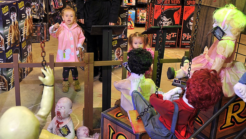 The Charland sisters, Avery, 3, and 2-year-old Sophia, are a little leary of the Zombie Babies display at Spirit Halloween in South Portland on Friday. They were there with their mother, Jessica Charland, who said her daughters have asked for somewhat tamer costumes; Sophie wants to be a cupcake and Avery wants to be a princess.