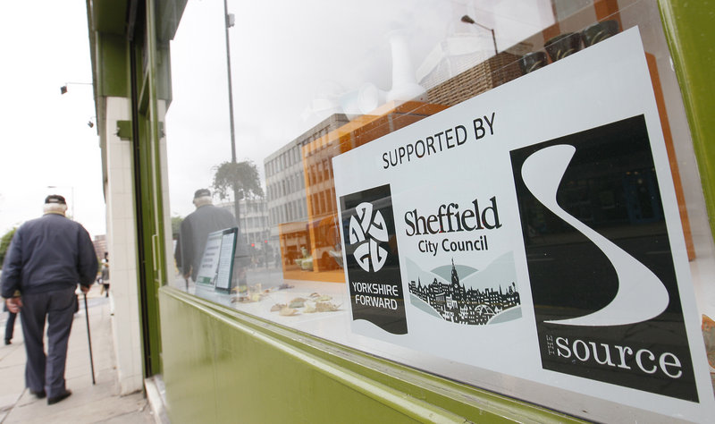 A man walks past an empty shop in a financially stalled redevelopment project in Sheffield, England, which now lets out shops left empty to local community artists.