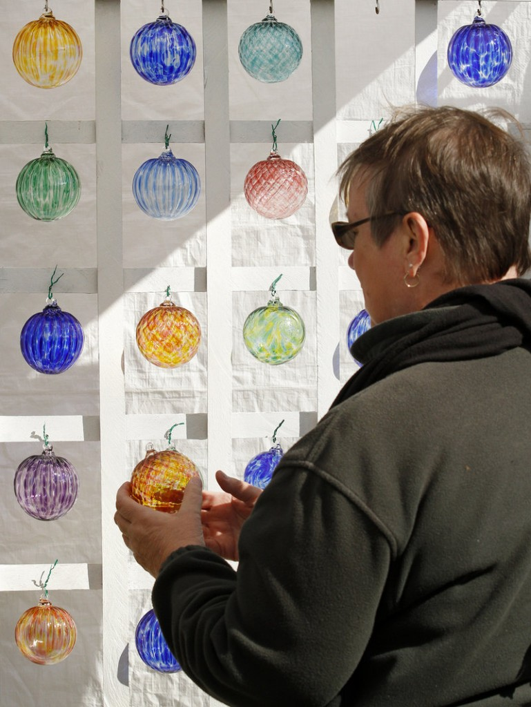 Penny Lightner of Hartford, Conn., takes a closer look at glass ornaments at a vendor booth at Harvestfest.