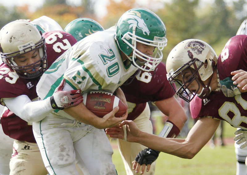 Casey Nava of Massabesic is stopped by Casey Wiseman, left, and Chris Dolewa of Thornton Academy during Thornton s 41-19 victory Saturday at Saco. The Golden Trojans improved to 6-1; Massabesic is 0-7.