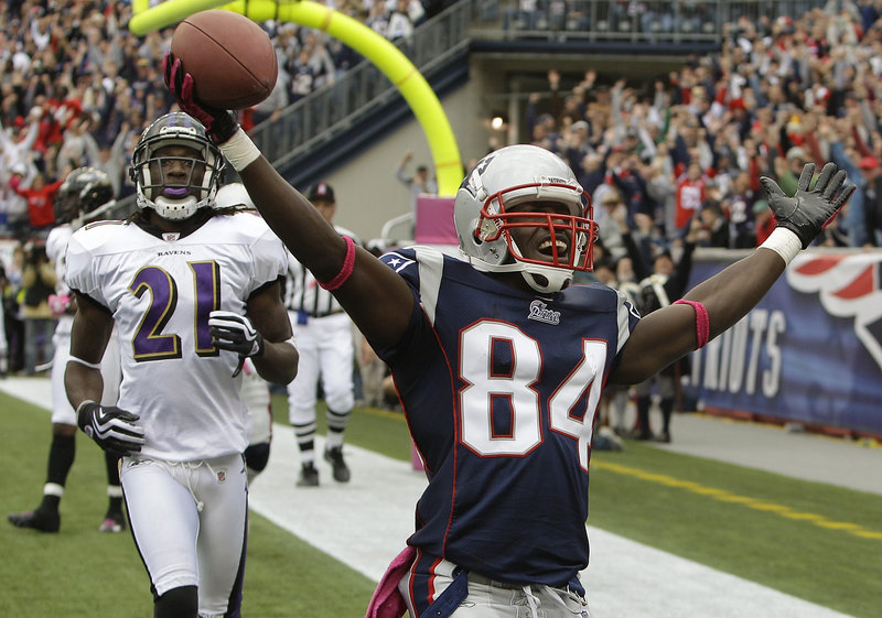 New England receiver Deion Branch celebrates a 5-yard touchdown reception over Baltimore cornerback Lardarius Webb in the fourth quarter Sunday. The catch and point-after kick cut Baltimore's lead to 20-17.