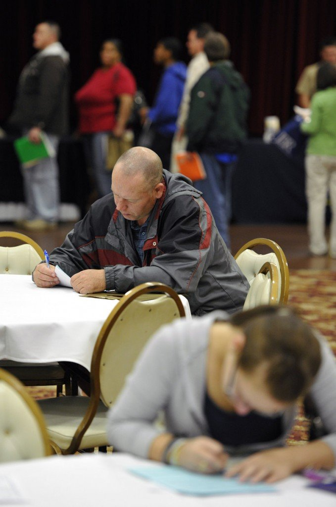Unemployed people fill out applications at a job fair in Illinois Oct. 5. A reader says not enough is being done for people like them.