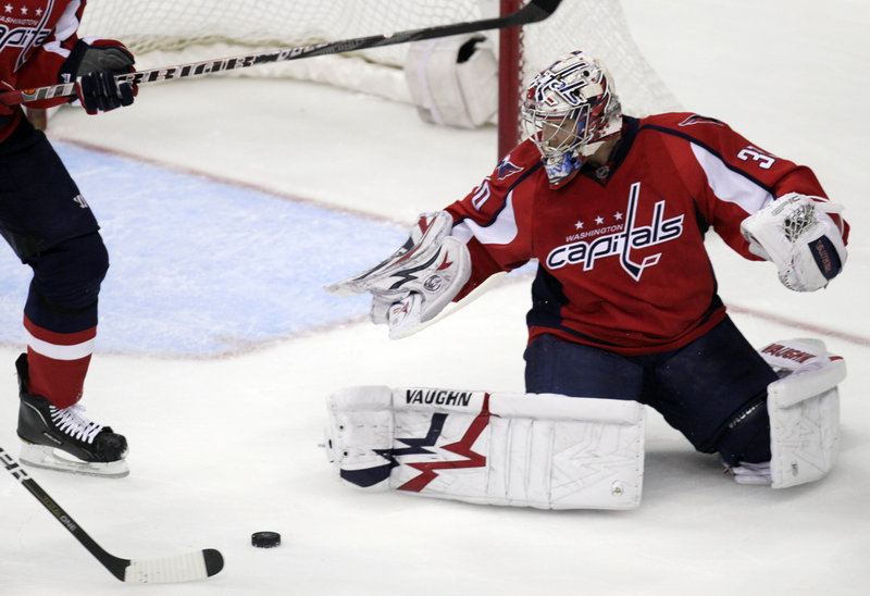Washington goalie Michal Neuvirth looks on Tuesday night as Boston left wing Milan Lucic, stick at left, scores during the first period of their game at the Verizon Center in Washington. The Capitals had won four straight.
