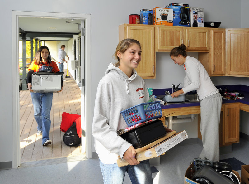 A small army of students from North Yarmouth Academy volunteers at the new Boys and Girls Club in Sagamore Village on Wednesday as part of Project: Reach Out. Here, 16-year-old Moira Lachance, center, carries a box filled with kitchen supplies, followed by Hennah Look, 13, who is lugging a new microwave oven. On the right is Sarah Burkey, 17, who volunteered to put away all the items around the sink. Sweeping the porch, background left, is Josiah Henderson, 14. North Yarmouth students traveled from Portland to Bath to Lewiston-Auburn to participate in community service projects, which included clearing trails, yardwork and planting trees. The success of Project: Reach Out last spring convinced school officials to make the event a biannual occurrence.