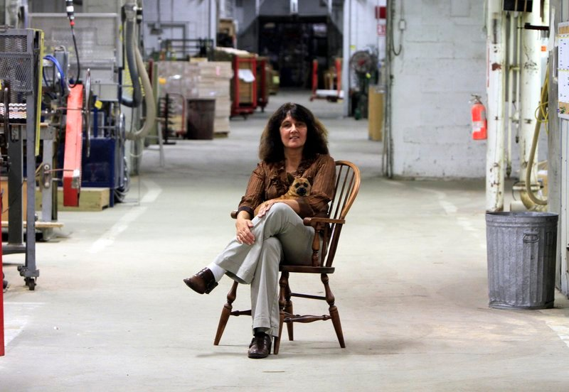 Louise Jonaitis and her dog Butterscotch sit in the recently reopened Saunders Bros. plant. Jonaitis has bought four mills saying that she intends to bring the plants back to life.
