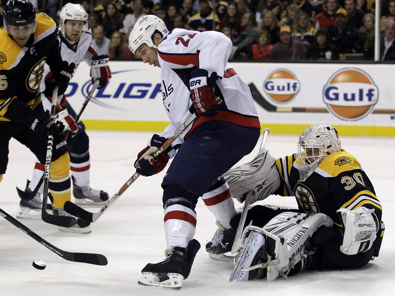Tim Thomas, who lost his shutout with a poor clearing pass, keeps an eye on the puck Thursday night as Mike Knuble of the Washington Capitals creates traffic in front of the net during the first period. The Bruins won, 4-1.