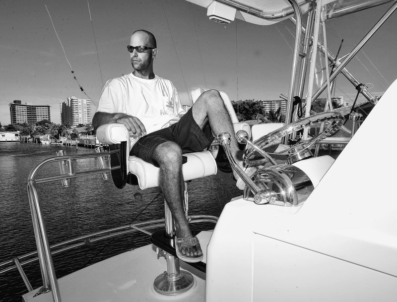 Former mortgage industry executive Jason Altneu, seen in South Florida on his boat last August, now has two jobs – charter boat captain and independent insurance agent – as many professionals look for new fields because their old career paths have disappeared.