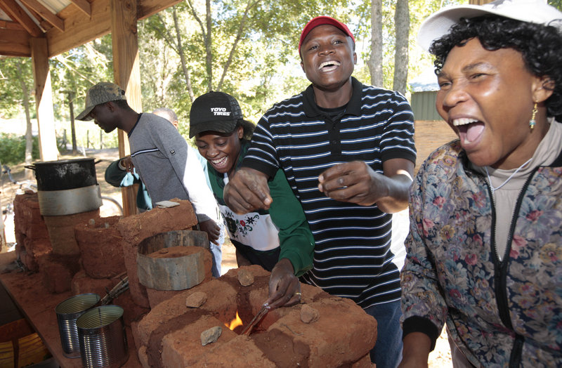 Ifeanyi Nwanaforo, center, of Nigeria reacts along with Rev. Grace Akunor, right, of Ghana and Sylvie Kamuna, second from left, of the Democratic Republic of Congo after starting a fire in their homemade brick oven during training at Servants in Faith and Technology in Lineville, Ala.