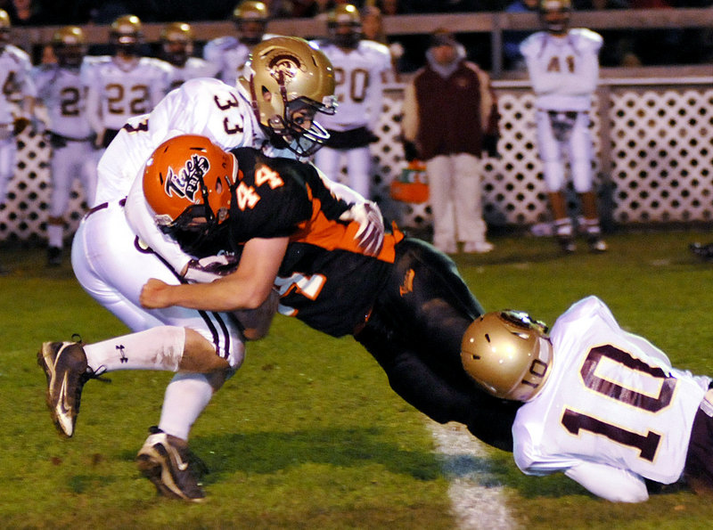 Nick Gagne of Biddeford stretches for extra yards Friday night while being brought down by Josh Remmes, left, and Nate Colpitts of Thornton Academy during their rivalry game at Waterhouse Field. Biddeford won 27-22, beating the Golden Trojans for the first time in five years.