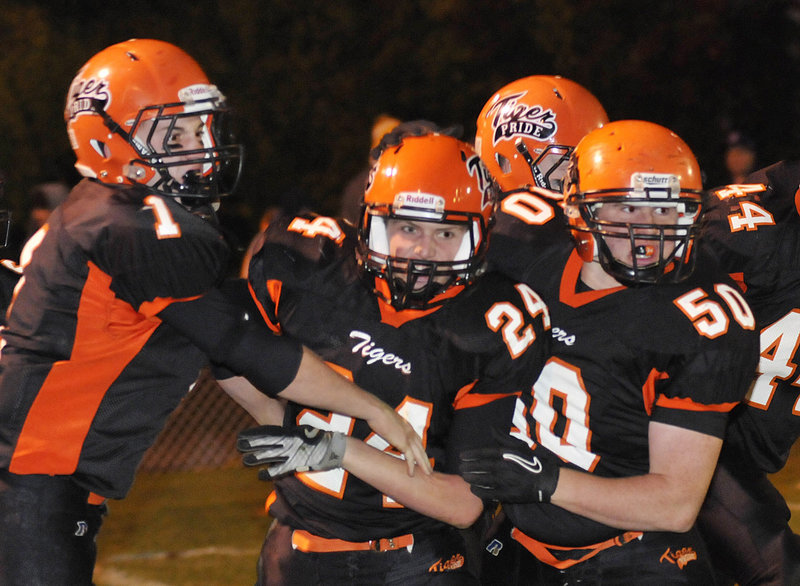 Patrick Wilson of Biddeford, center, is congratulated by J.D. Shannon, left, and Leonard Dube after scoring a first-period touchdown Friday night. The Tigers went on to beat Thornton Academy 27-22 in their rivalry game at Waterhouse Field.