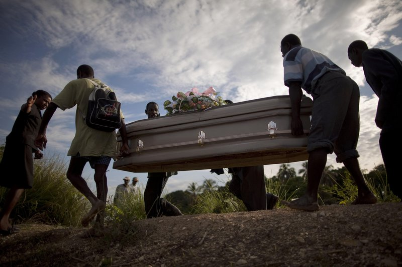 Haitians carry a coffin containing the remains of a relative who died of cholera in Robine, Haiti, on Saturday. A cholera outbreak threatens to outpace aid groups hoping to keep the disease from reaching the camps of earthquake survivors in Port-au-Prince.