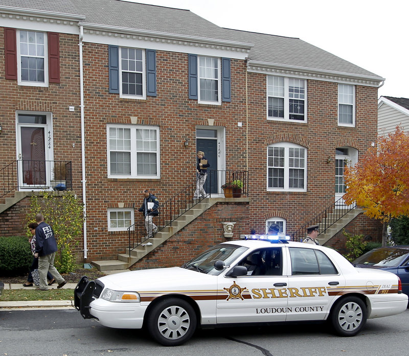 FBI and law enforcement investigators leave the home of Farooque Ahmed in Ashburn, Va., on Wednesday. Ahmed, who emigrated to the U.S. in 1993 and later became a citizen, is charged with trying to help people he believed were al-Qaida operatives planning to bomb subway stations around the nation's capital, the FBI said.