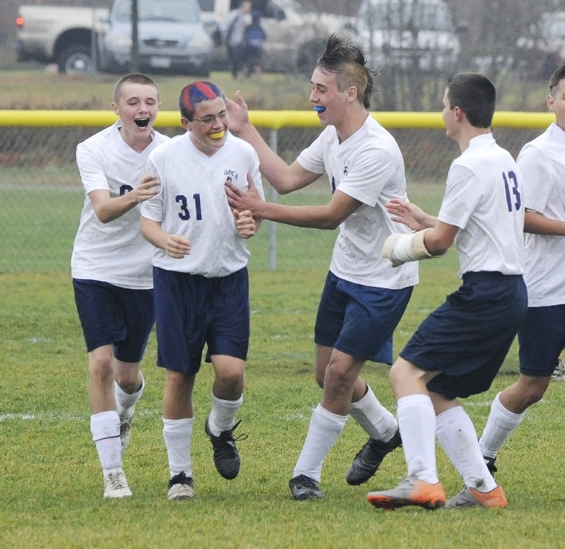 Sam Whiting of Greater Portland Christian is welcomed by teammates after scoring a goal in the second half.