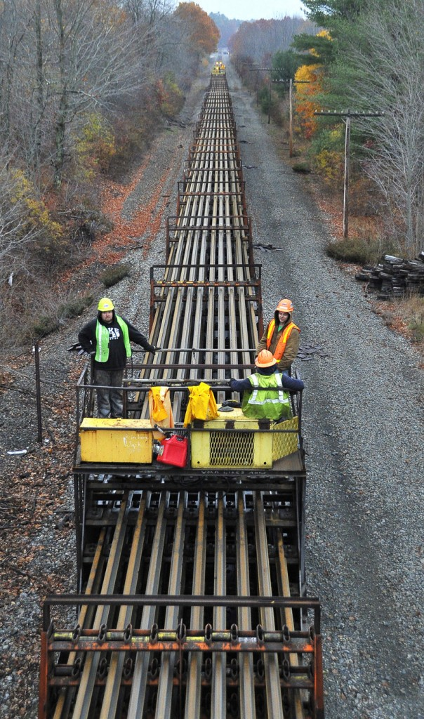 This crew, shown between Falmouth Road and Route 100 in Falmouth on Wednesday, will be responsible for depositing strings of welded rail line on each side of the bed for assembly in the spring.