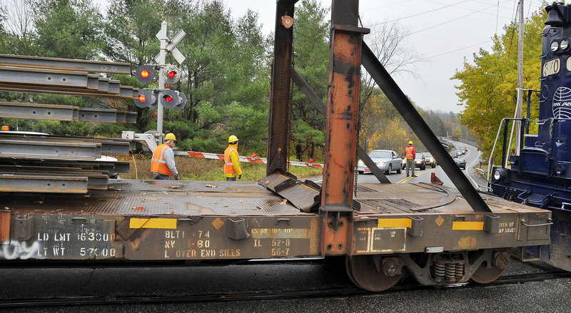 Traffic is stopped at the Leighton and Falmouth Road crossing in Falmouth for about 45 minutes Wednesday as rails are slipped off the back of a train in preparation for assembly in the spring.