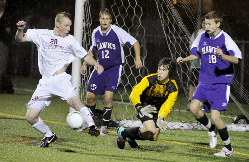 Paul Wennberg of Cape Elizabeth, left, provides a screen Wednesday night as a shot by teammate Blake Barritt skips through for a goal. Defending for Marshwood are goalie Jackson Towle, with Thomas Kent, 12, manning a post. Cape Elizabeth won 5-0 at home.