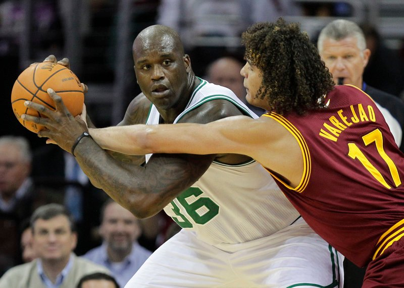 Anderson Varejao of the Cavaliers, right, tries to poke the ball away from Shaquille O'Neal of the Celtics during Cleveland's 95-87 victory in its season opener Wednesday night.