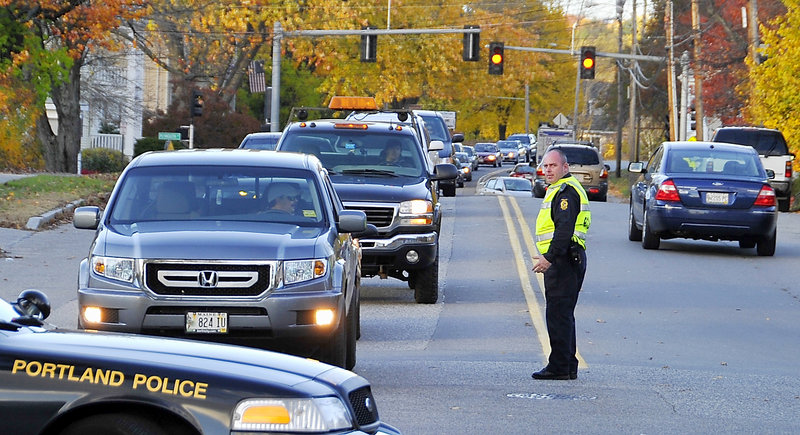 Traffic backs up Thursday at the Allen Avenue crossing as a train slowly passes. Officer Chris Coyne told drivers they could wait 45 minutes or find another route.