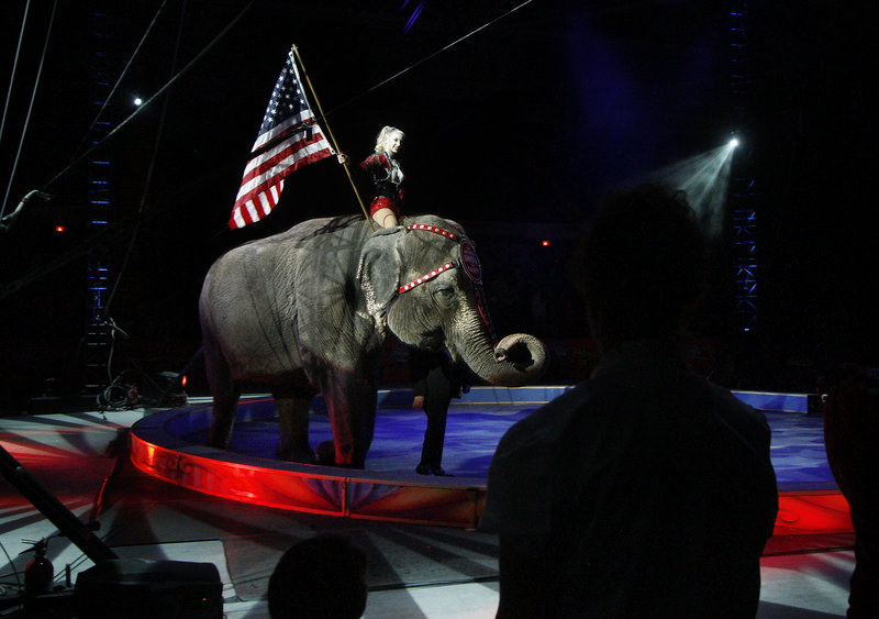 Performer Jamie Leigh carries the American flag atop one of the elephants during the opening night festivities.