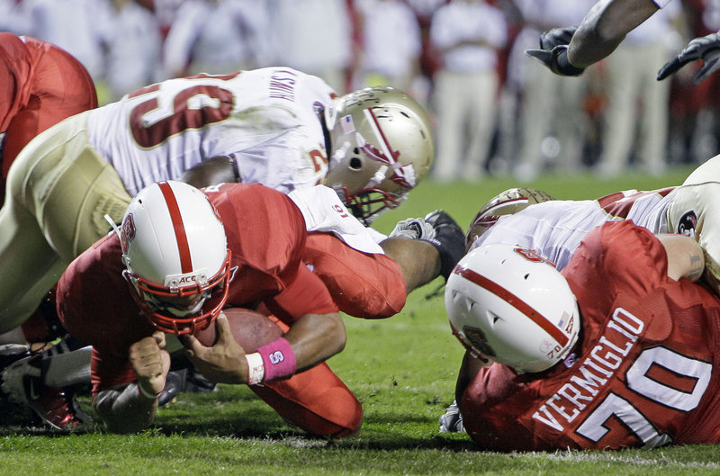 North Carolina State quarterback Russell Wilson dives past Florida State's Kendall Smith, left, for a touchdown as Jake Vermiglio blocks during Thursday night's game at Raleigh, N.C. Wilson ran for three scores in a 28-24 victory.