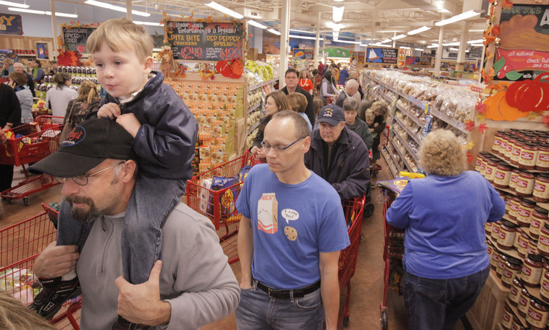 Alex Hyfield, 3, sits on the shoulders of his father, Chris Hyfield, while they wait in one of the checkout lines at the new Trader Joe's store in Portland on Friday. Throngs of Trader Joe's devotees jammed the store for its grand opening.