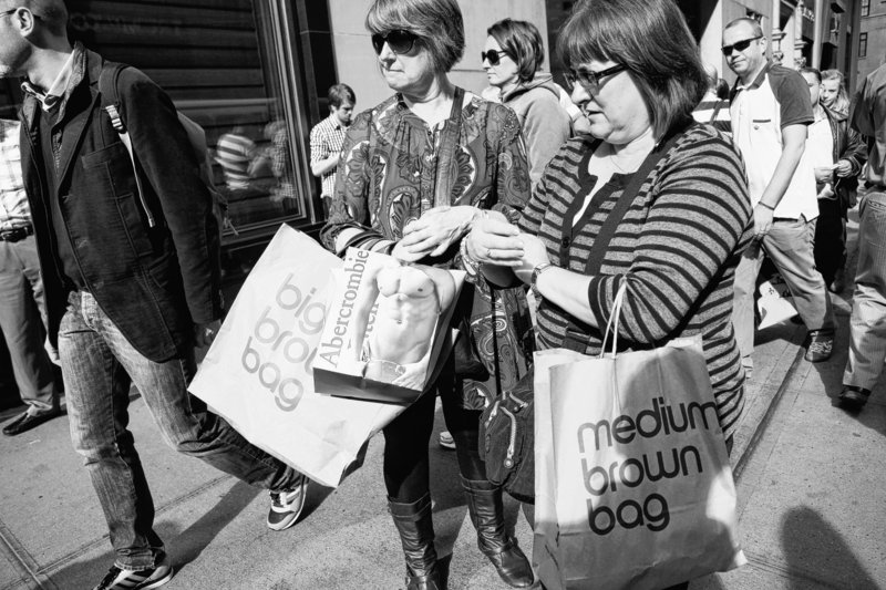 Women carry shopping bags on Fifth Avenue in New York. The economy grew at a slightly faster pace over the summer as Americans spent more, the Commerce Department said.