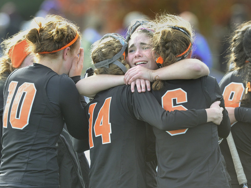 Kylie Dalbec hugs two North Yarmouth Academy teammates Saturday after the Panthers captured the Class C field hockey title by beating Foxcroft Academy.