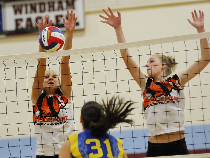 Bailey Cote, left, of Biddeford goes high for a block with help from Alyssa Drapeau during the Class A volleyball state final Saturday against Falmouth at Windham High. The top-ranked Tigers clinched their first title with a 3-0 win.