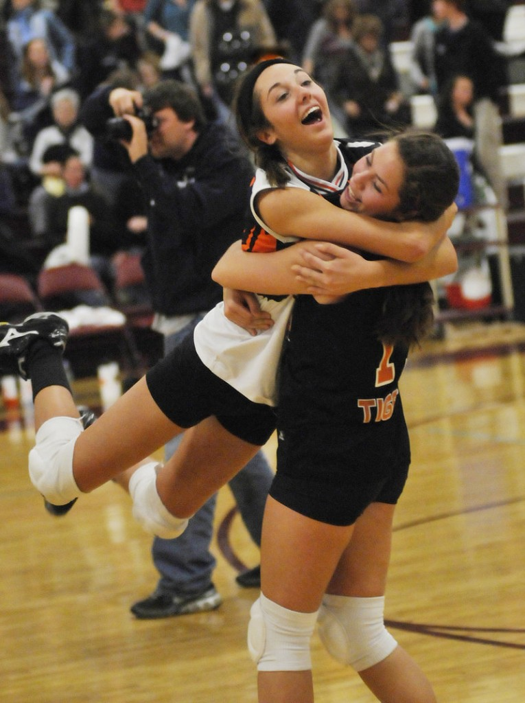Renee Trottier leaps into the arms of teammate Katelyn Lebreux as they celebrate a victory over Falmouth in the Class A volleyball state final Saturday at Windham High School.