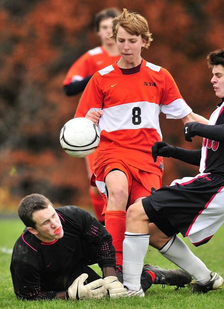 North Yarmouth Academy keeper Jordan Zembroski, left, blocks a shot by Hall-Dale s Kevin Zembroski, right, as NYA s Jackson Cohan-Smith tries to clear the rebound.