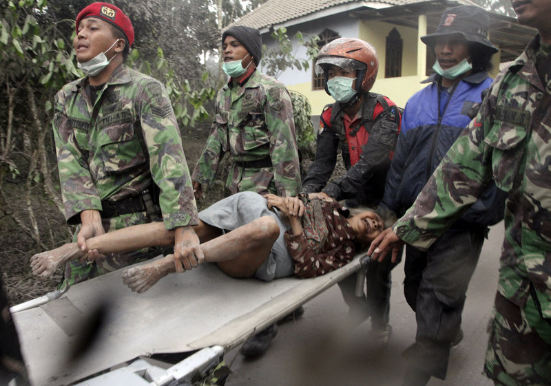 Indonesian soldiers evacuate an elderly woman who refuses to leave her house in Ngerangkah, Yogyakarta, Indonesia, on Saturday. Indonesia's military forced villagers off the slopes of the country's most volatile volcano Saturday as it unleashed a new powerful explosion.