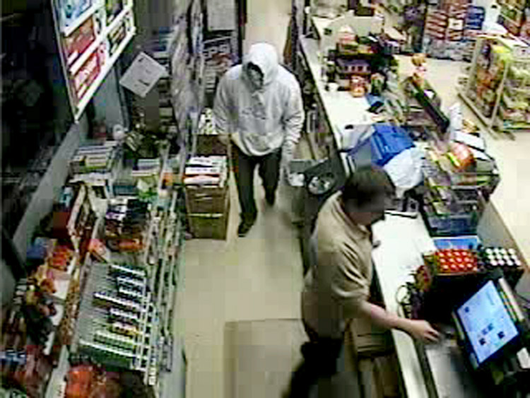 Security camera photo shows robbery suspect wearing hooded sweatshirt.