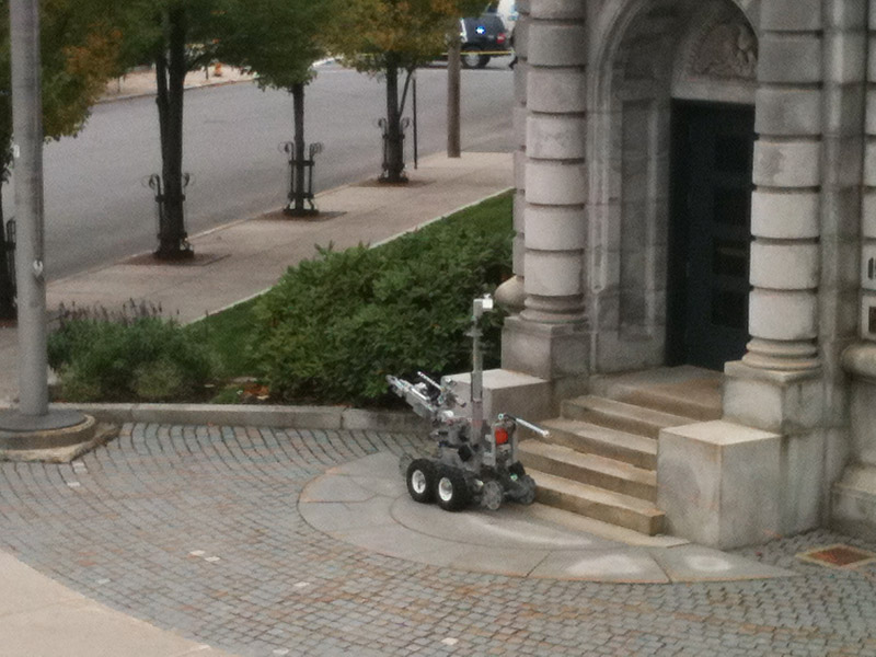 A police robot is maneuvered into position to examine a suspicious package found near the entrance of the federal courthouse in Portland today.