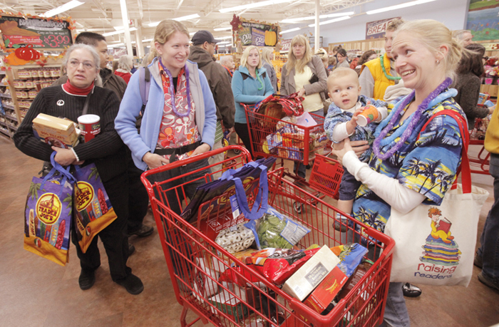 Clad in Hawaiian shirts, Emily Hickey of Gorham, right, holds her son Clayton, 10 months, and talks with her friend Liz Hornor while waiting in the checkout line at Trader Joe's in Portland. The long-awaited store opened this morning and drew a large crowd of shoppers.