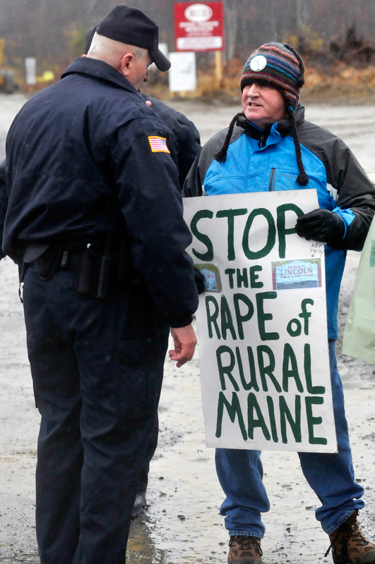 Protester Brad Blake of Portland who was with Friends of Lincoln Lakes is asked by a police officer to move off the property at the Rollins wind energy project in Lincoln Monday, Nov. 8, 2010.