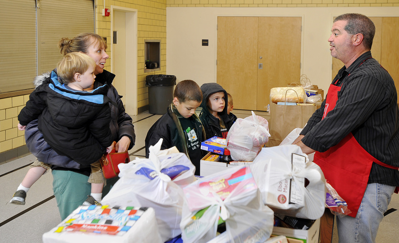 Volunteer David Menard chats with Gloria Dennison as she and her children pick up Thanksgiving food donations at the Salvation Army building on Cumberland Avenue in Portland on Monday.