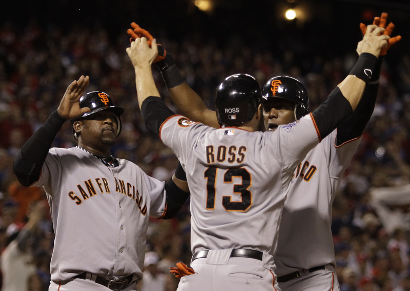 Cody Ross greets Edgar Renteria after Renteria hit a three-run homer in the seventh that gave the Giants the runs to win the game and clinch the World Series.