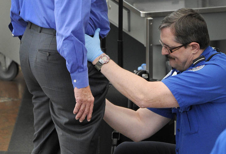 A Transportation Security Administration agent performs an enhanced pat-down on a traveler at a security area at Denver International Airport recently.