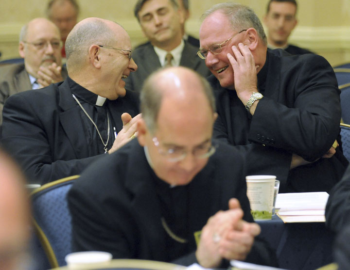 Bishop Roberty Vasa, left, of Baker, Ore., congratulates Archbishop Timothy Dolan, right, of New York after Dolan was elected president of the U.S. Conference of Catholic Bishops during the conference's annual fall meeting today.