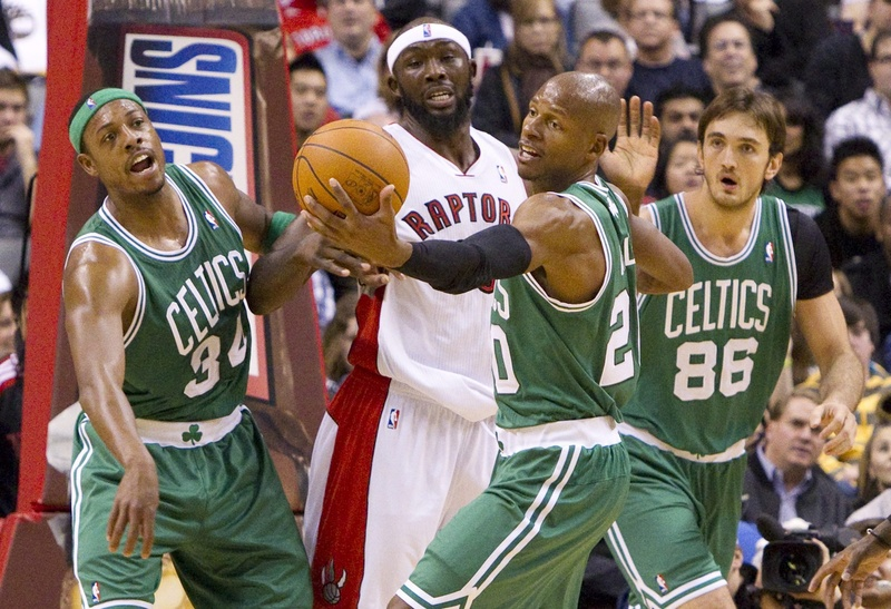 Toronto Raptors' Reggie Evans fights for a loose ball with Paul Pierce, left, Ray Allen, and Semih Erden of the Celtics in today's game at Toronto. The Raptors won, 102-101.