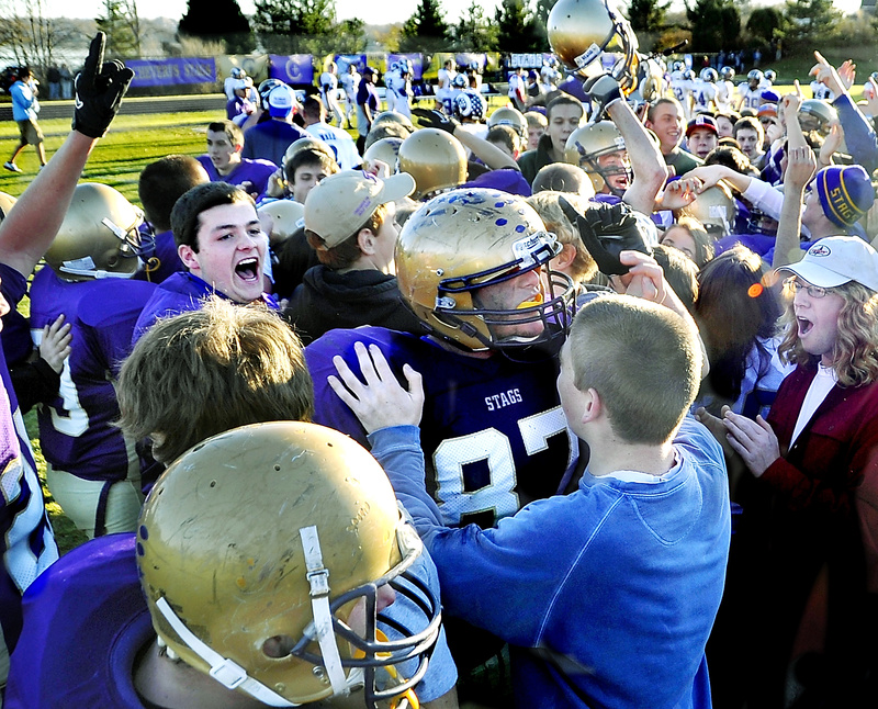 Fans and other team members swamp Christian Deschenes of Cheverus after the Stags beat Deering by one point in the Western Maine Class A football championship at Cheverus today. Cheverus will play Bangor for the state title next Saturday at Fitzpatrick Stadium