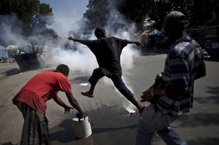 A demonstrator runs to avoid tear gas fired by police and UN soldiers during a protest in Port-au-Prince, Haiti, Thursday,. Following days of rioting in northern Haiti over suspicions that U.N. soldiers introduced a cholera epidemic that has killed more than 1,000 people, protesters in Haiti's capital clashed with police, lashing out at U.N. peacekeepers and the government, blocking roads and attacking foreigners' vehicles.