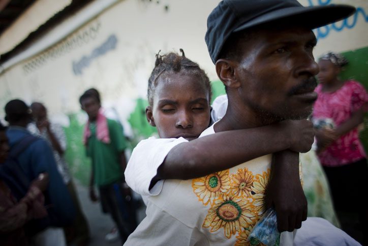 A young woman suffering cholera symptoms is carried by a relative to St. Catherine hospital, run by Doctors Without Borders, in the Cite Soleil slum of Port-au-Prince today. Thousands of people have been hospitalized for cholera across Haiti with symptoms including serious diarrhea, vomiting and fever and at least 1,100 people have died.