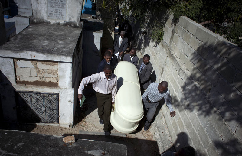 Relatives of Serge Ragmond, 49, who died of cholera, carry his coffin during his burial at the cemetery in Port-au-Prince today.