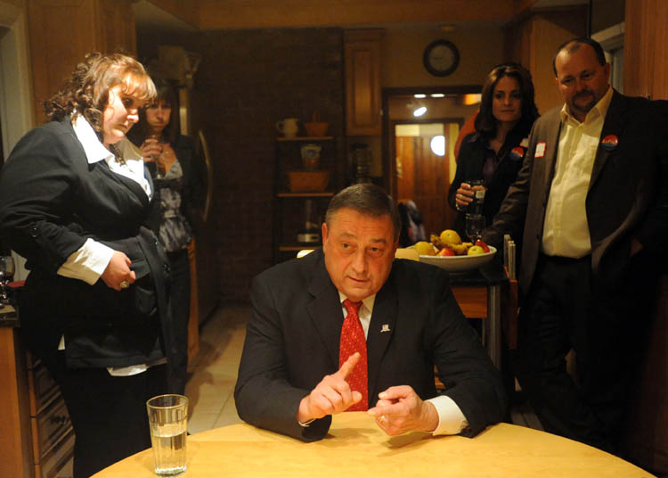 Paul LePage answers questions from Morning Sentinel reporter Amy Calder in his kitchen at his Waterville residence surrounded by family as poll numbers roll in late Tuesday night.