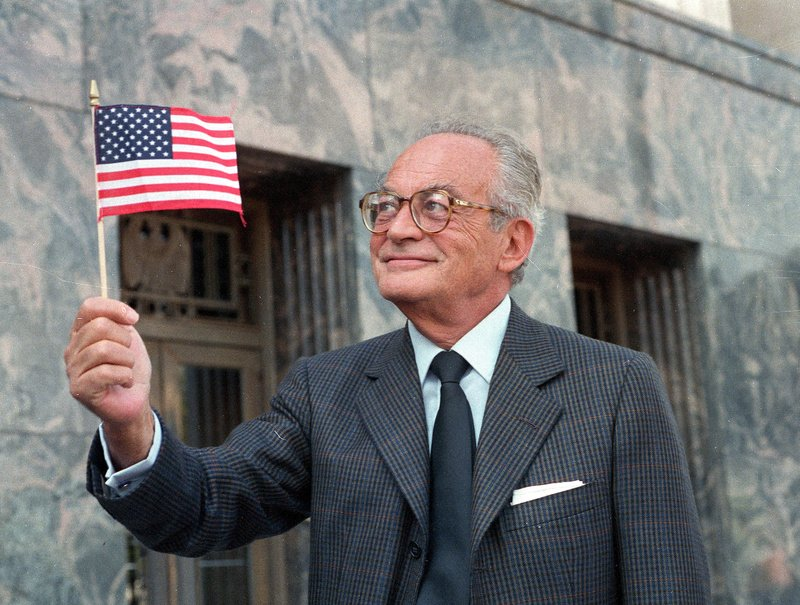 """Film producer Dino De Laurentiis holds an American flag outside the Los Angeles Federal Courthouse after becoming a U.S. citizen in 1986. A producer of """"Serpico,"""" """"Barbarella"""" and """"Death Wish,"""" he died Wednesday at age 91."""