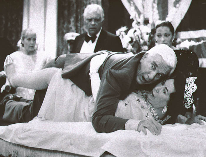 A 1988 publicity photo of Leslie Nielsen, center top, with actress Jeannette Charles, portraying the Queen of England in a scene from